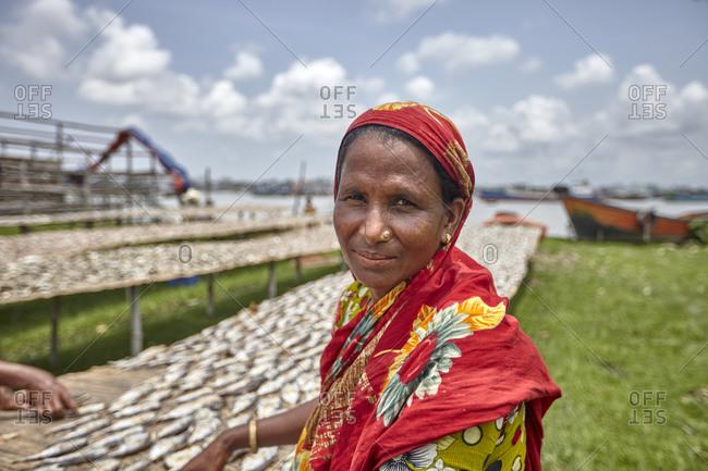 Chittagong, Bangladesh - May 11, 2013: A woman working at a dry fish factory on Karnaphuli River bank, Chittagong, Bangladesh