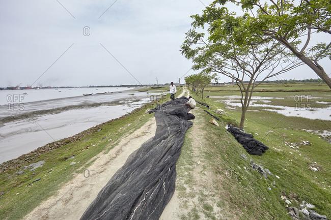 Chittagong, Bangladesh - May 12, 2013: Men repairing a fish net on a dirty road alongside the Karnaphuli River