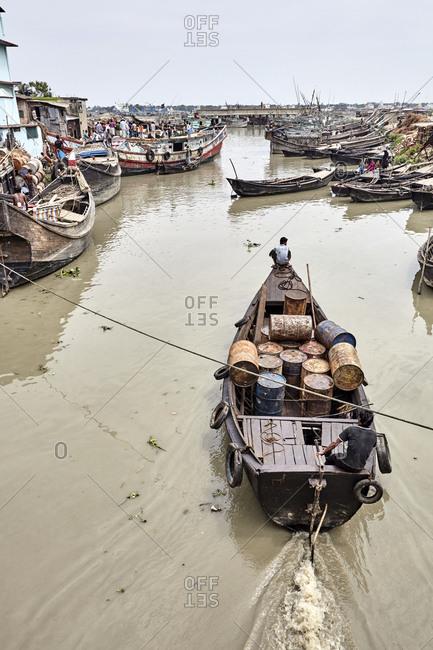 Chittagong, Bangladesh - May 13, 2013: A man navigating his wooden boat at Chaktai Khal on the River Karnaphuli