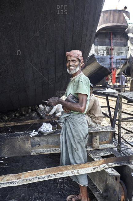 Chittagong, Bangladesh - May 11, 2013: Men working on a traditional fishing boat at a shipyard by the Karnaphuli River