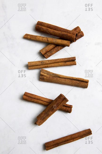 Overhead view of cinnamon sticks on a white marble background