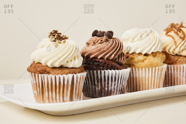White tray of yummy variety of cupcakes flavors on a cream background