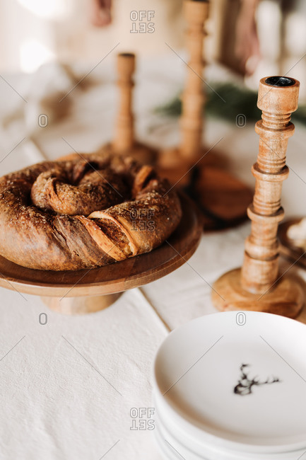Round rustic homemade loaf of bread set on a wooden stand on table beside candlestick holders and plates