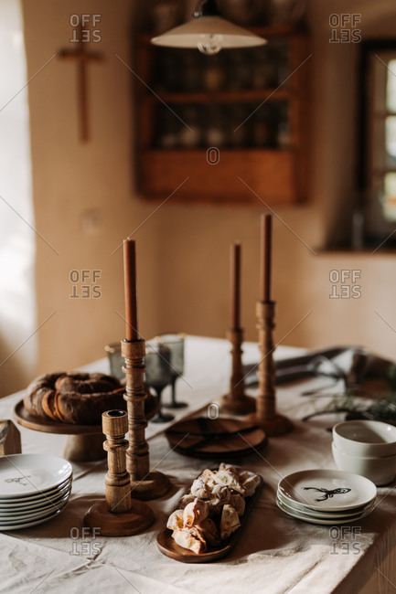 Rustic holiday table setting with baked goods and wooden candlestick holders