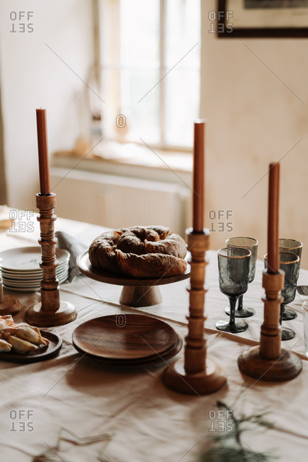 Holiday gathering table with baked goods and wooden candlestick holders