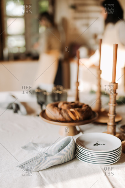 Stack of plates by baked goods and wooden candlestick holders on a holiday gathering table