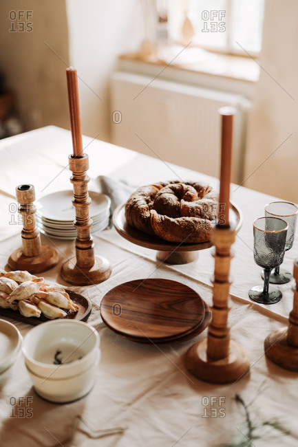 Holiday table with baked goods and wooden candlestick holders set for a party