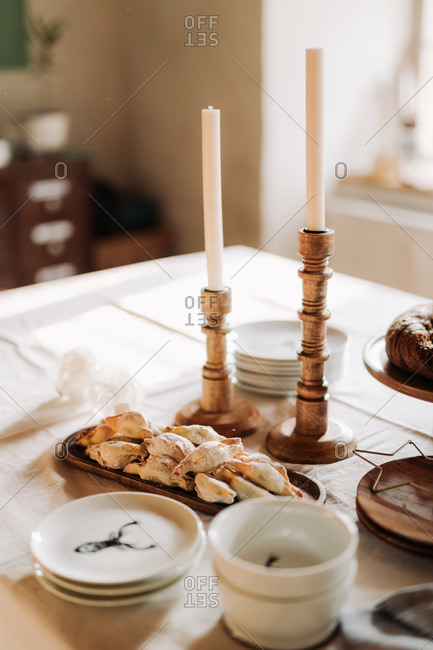 Pastries on a holiday gathering table with wooden candlestick holders