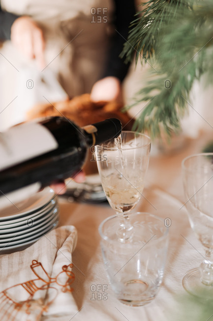 Wine being poured into a glass on a holiday table