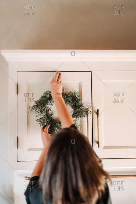 Woman hanging a Christmas wreath on a white cabinet door
