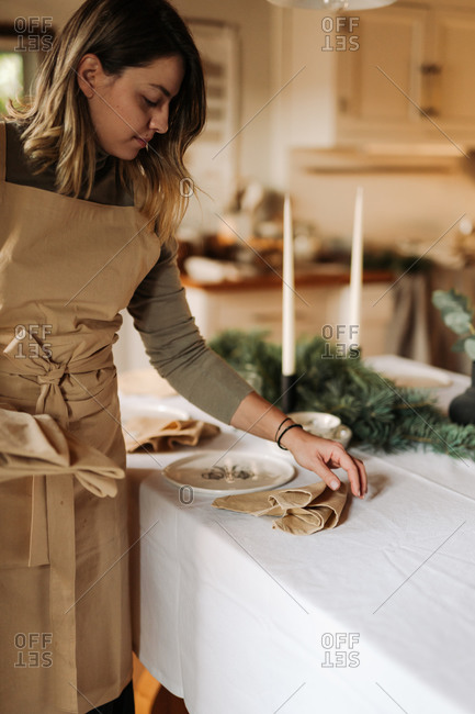Young woman neatly folding tan linen napkins on a table being set for a holiday party