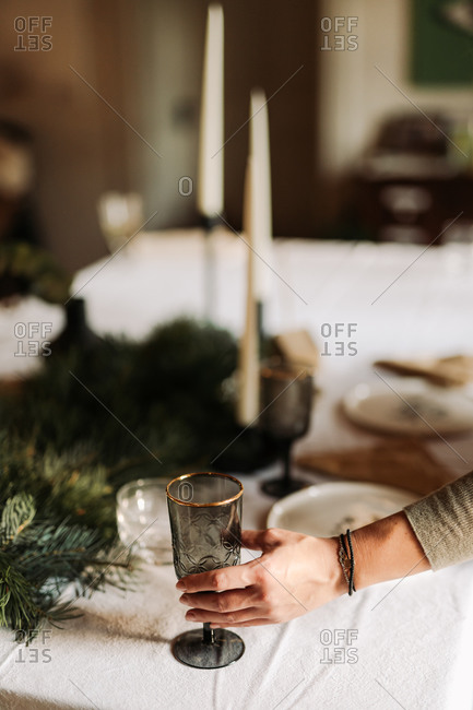 Woman placing wine glasses on a table being set for a holiday party