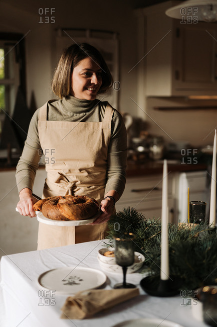 Young woman serving a homemade bread loaf for a holiday party