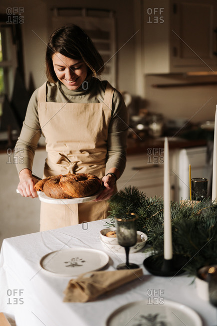 Young woman placing a homemade bread loaf on a table for a holiday party