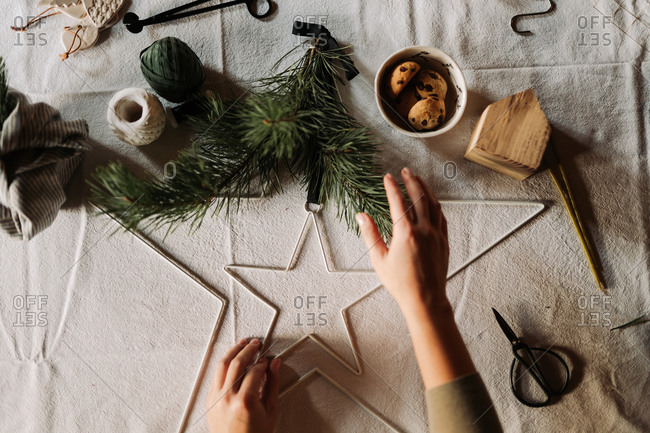 Overhead view of a crafter making Christmas decorations on table with linen tablecloth