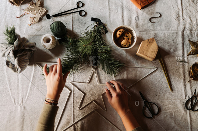Crafter making Christmas decorations on table with linen tablecloth viewed from above