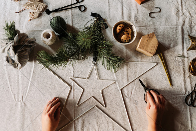 A star Christmas decoration being made on table with linen tablecloth viewed from above