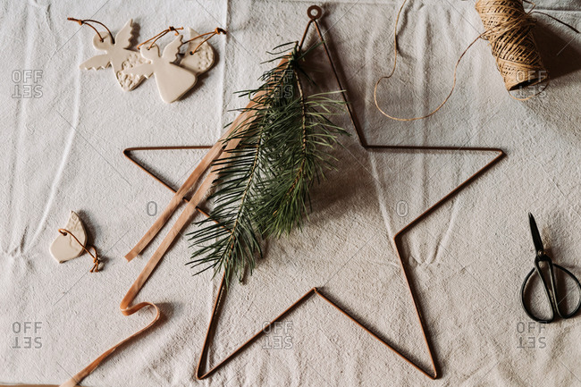 Overhead view of a star shaped Christmas decoration on table with linen tablecloth