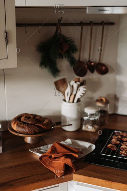 Homemade bread loaf on wooden kitchen counter by cooling baked apples