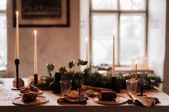 Holiday gathering table with baked goods and lit candlesticks