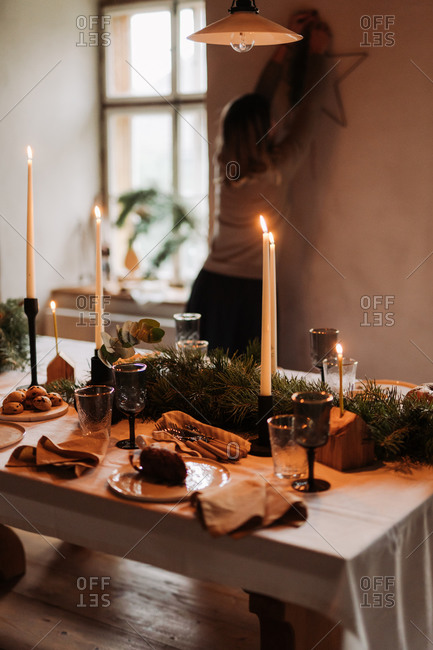 Holiday gathering table with baked goods and lit candlesticks with woman putting decoration on wall in background