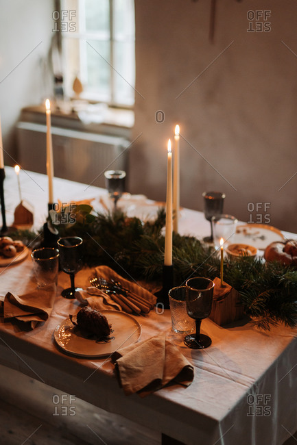 Christmas dinner table with baked goods and lit candlesticks