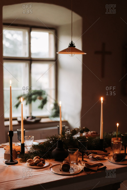 Cozy Christmas dinner gathering table with baked goods and lit candlesticks