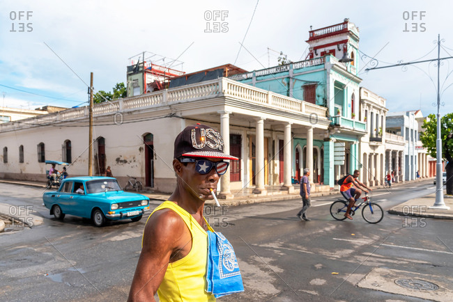 August 28, 2019: Man smoking with American flag cap and glasses on the streets of Cienfuegos. Cienfuegos, Cuba