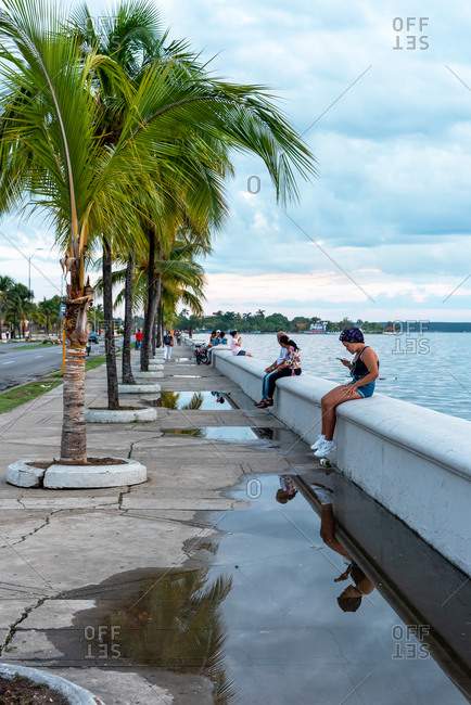 August 28, 2019: People sitting on the malecon of Cienfuegos spending the afternoon
