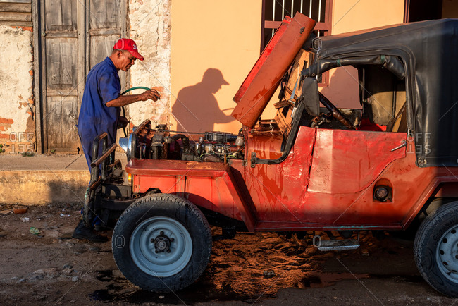August 24, 2019: Man cleaning old Car. Trinidad, Cuba