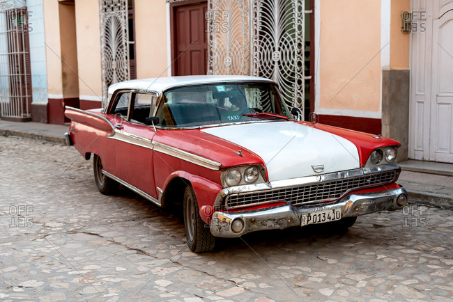 August 24, 2019: Street scene with an old American car on the cobblestone street. Trinidad, Cuba