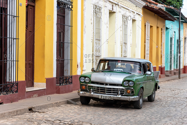 August 25, 2019: Street scene with an old American car on the cobblestone street. Trinidad, Cuba