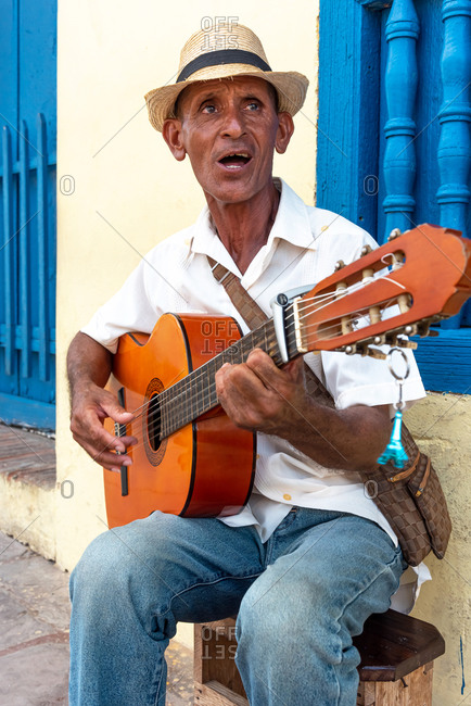 August 26, 2019: A Cuban man sings and plays his guitar on a street. Trinidad, Cuba