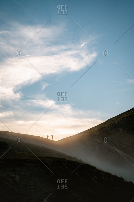 Silhouette of a young couple taking photos of the landscape while hiking