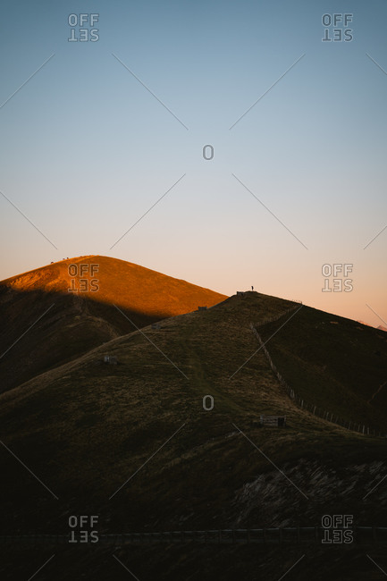 Hiker standing on top of a hill taking photos of the landscape during sunset