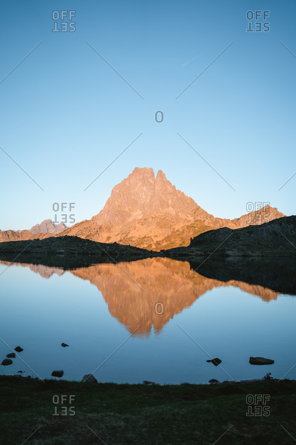 Big mountain reflected on a calm lake during sunset in French Pyrenees