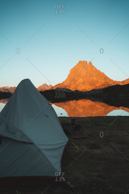 Hiking tent set on the shore of a lake with glowing mountain on the background