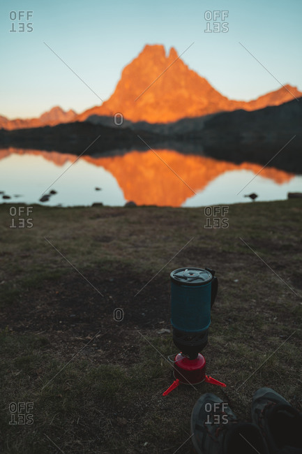 Hiking shoes and backpacking stove on the shore of a lake in French Pyrenees during sunset