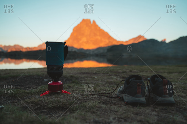 Hiking shoes and backpacking stove on the shore of a lake in French Pyrenees during sunset with glowing mountain in background