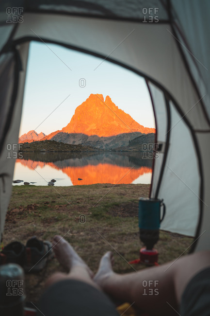 View from inside of a tent of Pic du Midi reflected in Ayous lake during sunset