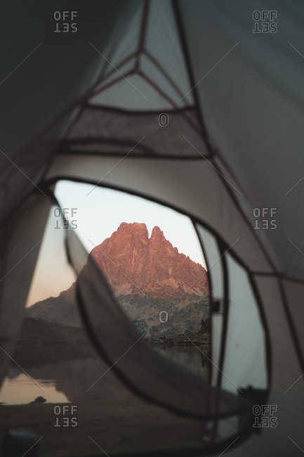 Hikers hand opening the tent in the morning to watch the sunrise