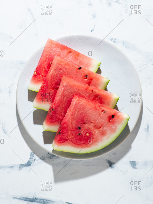 Sliced watermelon served on ceramic white plate over white background