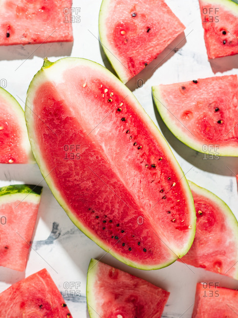 Overhead view of sliced watermelon over white background