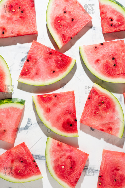 Overhead view of sliced watermelon served on white background