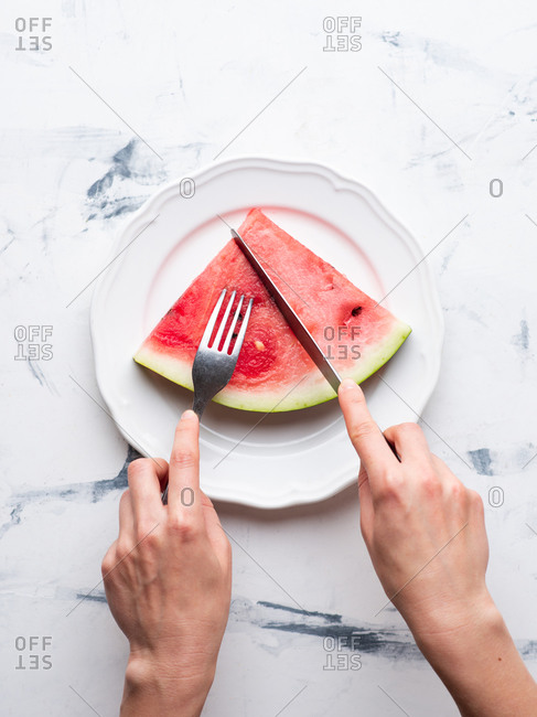 Sliced watermelon served on ceramic white plate over white background. Female hands holding fork and knife
