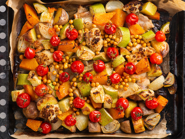 Roasted root vegetables cooked with tomatoes, onion and chickpea on a roasting tin