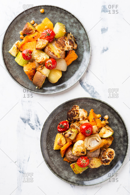 Overhead view of roasted root vegetables cooked with tomatoes, onion and chickpea