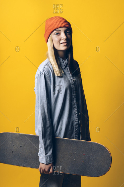 Young expressive girl holding a skateboard.