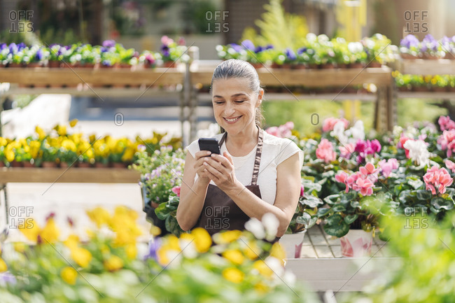 Beautiful middle aged woman working in plant nursery and using phone.