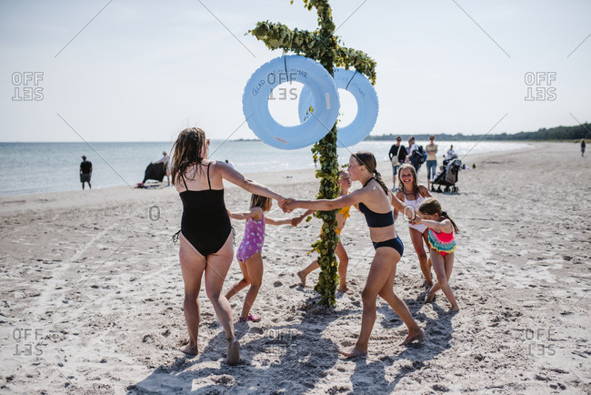 Mother with daughters dancing around maypole on beach